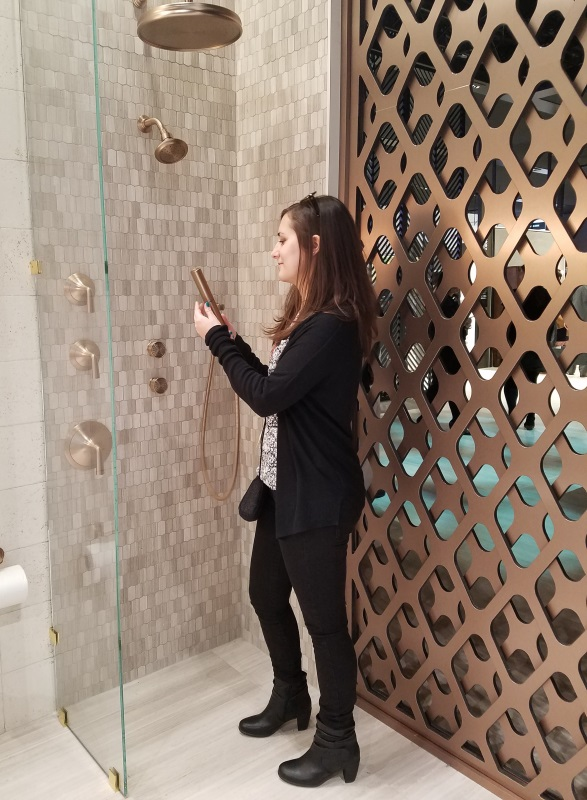 Jessica checking out a shower fixture display at the 2017 Kitchen and Bath Industry Show