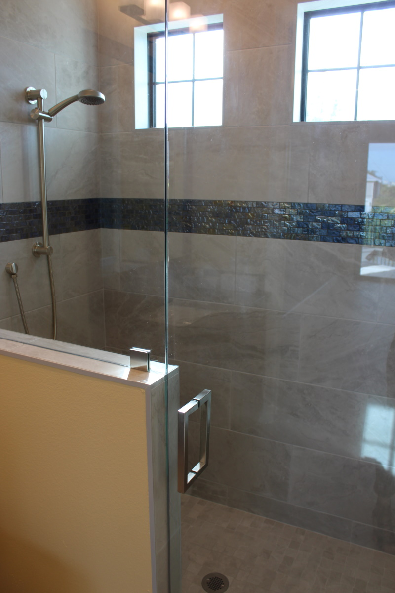 Shower stall with clear glass front and tile sides and back. Two windows higher up provide lots of natural lighting