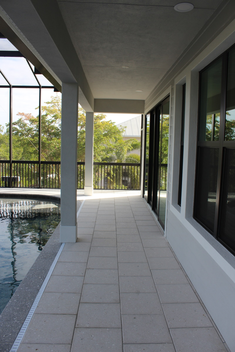 second story back patio covered lanai opens onto a pool