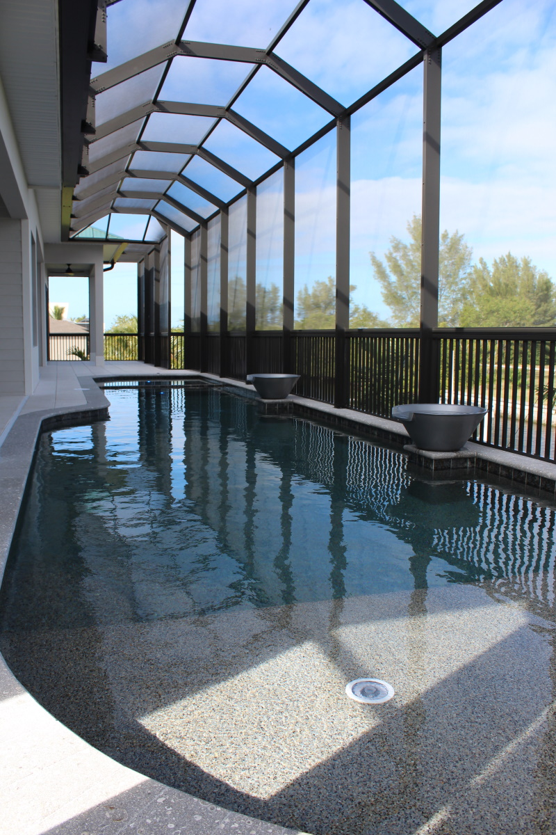 The shallow end of a Long pool on a back porch covered patio overlooking the canal with decorative pots on the pool's edge