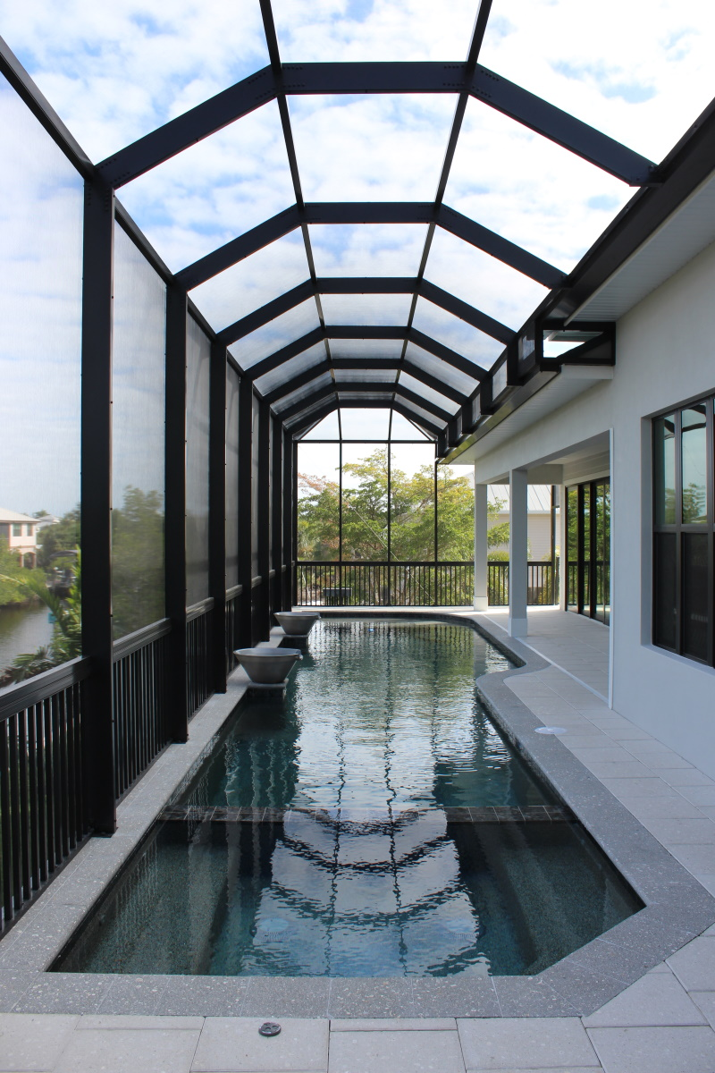 Long pool on a back porch covered patio overlooking the canal with decorative pots on the pool's edge