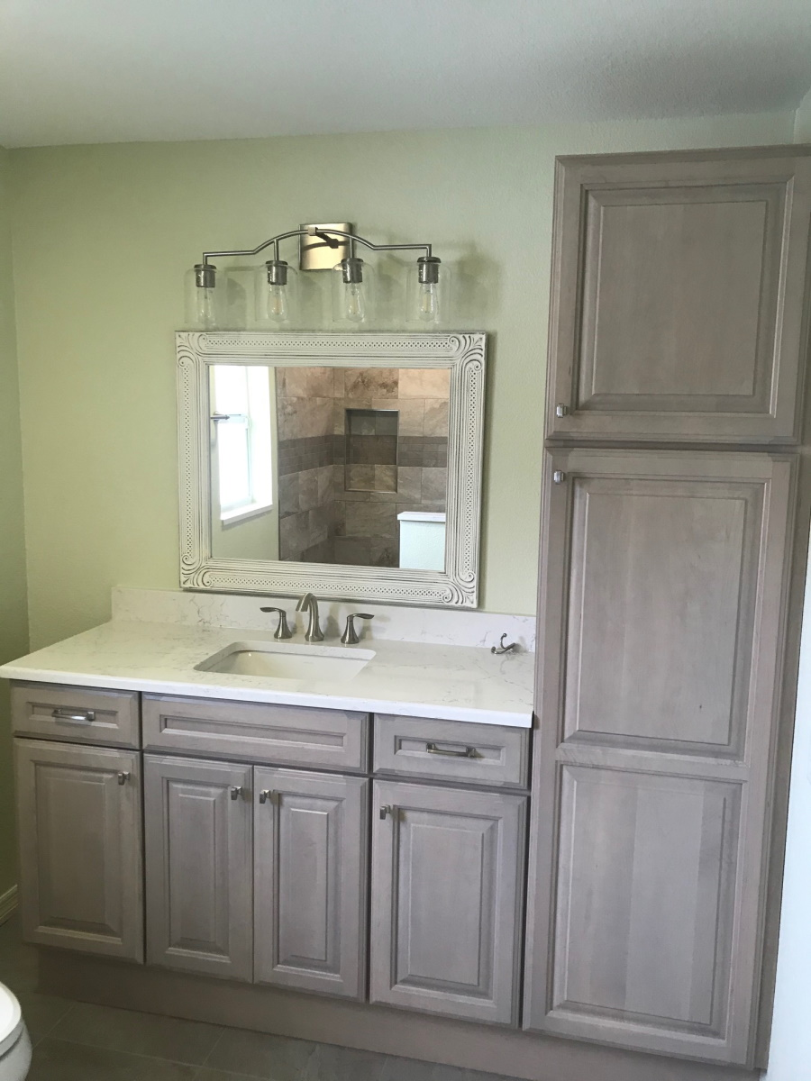 Natural wood bathroom cabinets with white marble counter and antique white vanity.