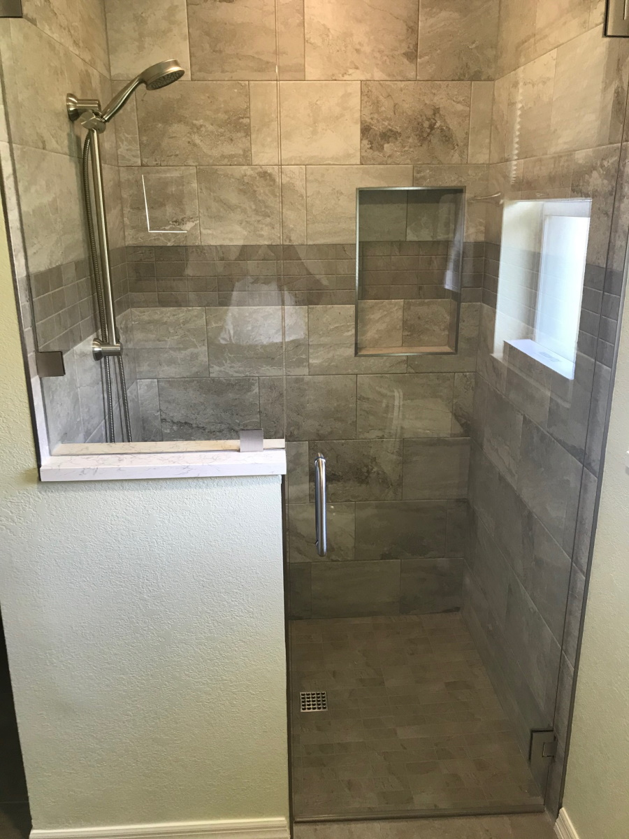 Shower stall with clear glass entryway. A small frosted window provides natural light and there is a in-wall shelf.