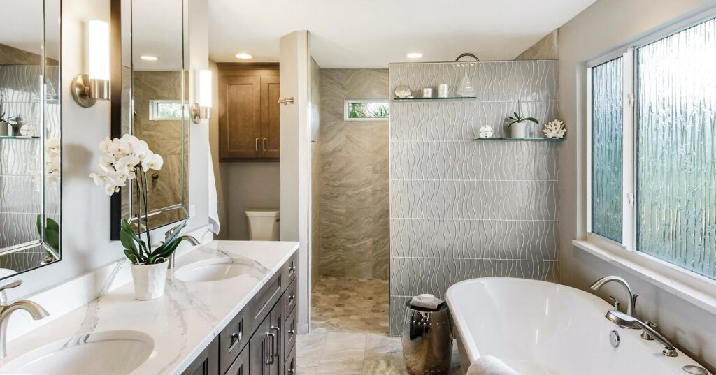 A SandStar Home bathroom project. A 2-sink white marble countertop with dark brown cabinetry sits near a standalone white porcelian bath tub. Frosted glass provides modern appeal.